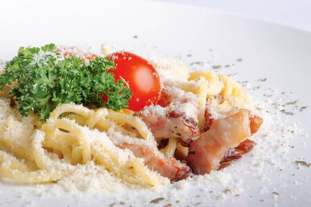 typical spaghetti alla carbonara  with raw egg and bacon. served on a white plate with grated Pecorino cheese. decorated with cherry tomato and parsley. side view close up