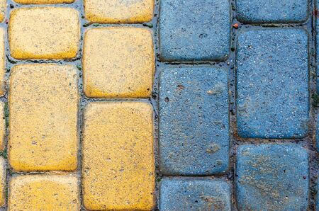 yellow and blue cobbles of pavement texture. stone masonry floor covering close up. top view of vertical wet grungy background Stock Photo