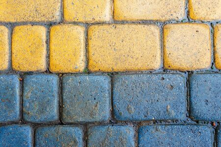 yellow and blue cobbles of pavement texture. stone masonry floor covering close up. top view of wet grungy background Stock Photo