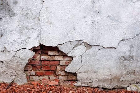 old white wall with cracks. damage on a brick wall. abstract ruin architecture texture. devastation background concept Stock Photo