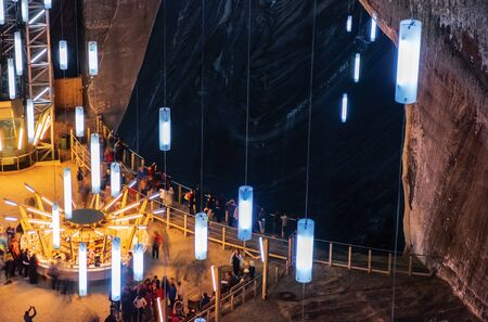 TURDA, ROMANIA - APR 30, 2018: Hall of Salt Mine Salina Turda museum. popular travel destination. people looking in to the pit