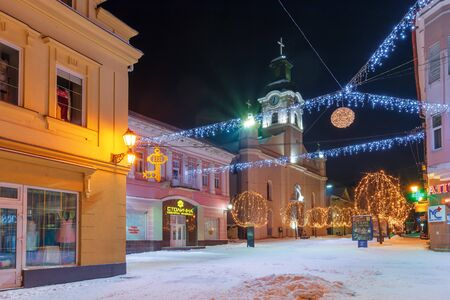 uzhhorod, ukraine - 06 JAN, 2019: winter night in town. wonderful blue and yellow christmas illumination. empty Voloshyna street covered in snow. catholic Cathedral in the distance