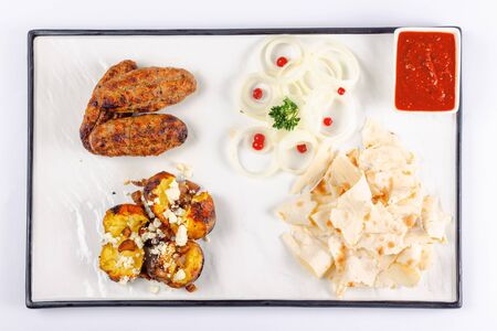 kebab and baked potato with cheese. onion circles and pita bread, red sauce on a white board. great snack dish for beer. top view flat layout Stock Photo