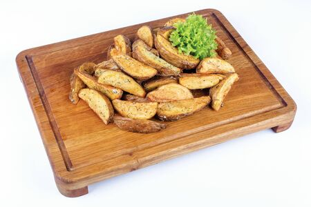 fried potato wedges or french fries. home made in rural style on served wooden board. healthy organic vegetarian food or beer snack