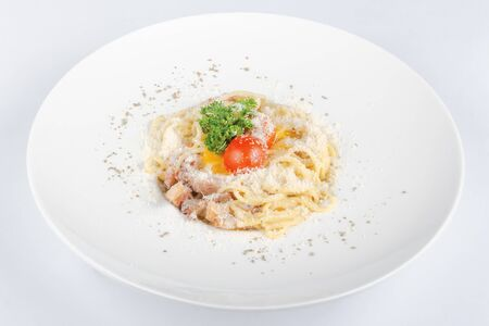 typical spaghetti alla carbonara  with raw egg and bacon. served on a white plate with grated Pecorino cheese. decorated with cherry tomato and parsley. top view