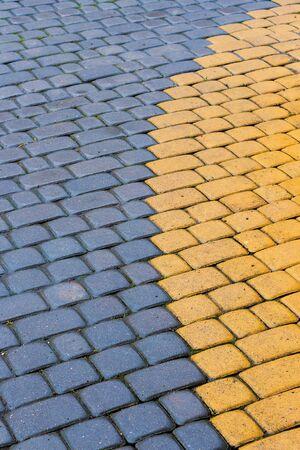 adoquines amarillos y azules de textura de pavimento. Revestimiento de suelo de mampostería de piedra en forma de arco. vista superior del fondo sucio mojado