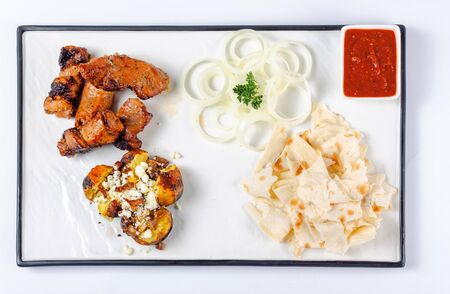 grilled pork and baked potato with cheese. onion circles and pita bread, red sauce on a white board. great snack dish for beer. top view, flat layout