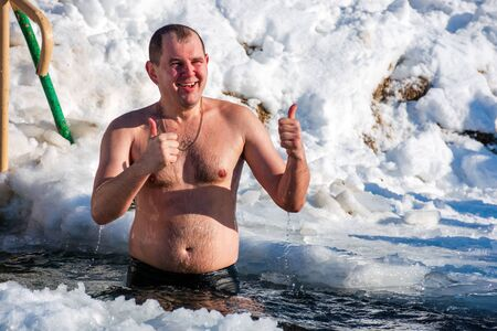 uzhhorod, ukraine - 19 JAN 2017: epiphany bathing on a sunny day. god blessed tradition of true orthodox Christians. dipping in the icy-hole with splashes and funny emotions. showing thumbs up