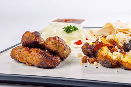 kebab and baked potato with cheese. onion circles and pita bread, red sauce on a white board. great snack dish for beer. close up view Stock Photo