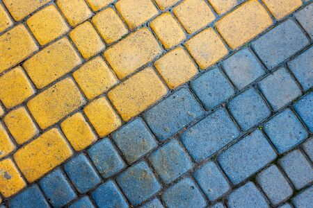 yellow and blue cobbles of pavement texture. stone masonry floor covering. top view of wet diagonal grungy background