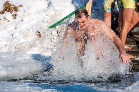 uzhhorod, ukraine - 19 JAN 2017: epiphany bathing on a sunny day. god blessed tradition of true orthodox Christians. dipping in the icy-hole with splashes and funny emotions. good health next year