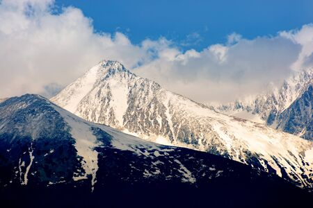 high tatras mountain ridge in springtime. snow capped rocky peaks in dramatic dappled sunlight beneath a clouds on a blue sky. place where earth meets sky concept