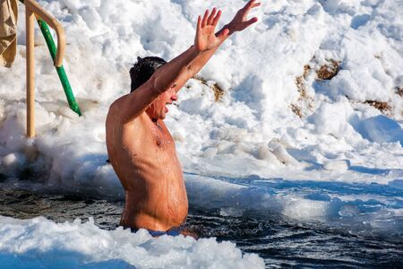 uzhhorod, ukraine - 19 JAN 2017: epiphany bathing on a sunny day. god blessed tradition of true orthodox Christians. dipping in the icy-hole with splashes and funny emotions. he is the winner sign