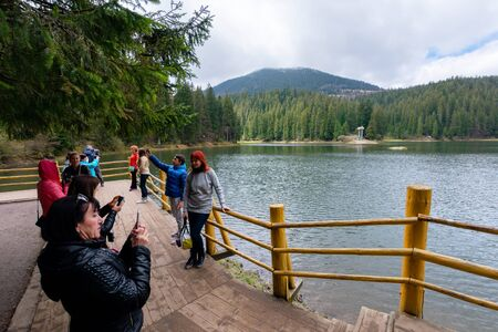 synevir national park, ukraine - MAY 09, 2017: people enjoying the beauty of Carpathian landscape. natural mountain lake attracts thousands of tourist to observe, relax and take selfies for memories Editorial