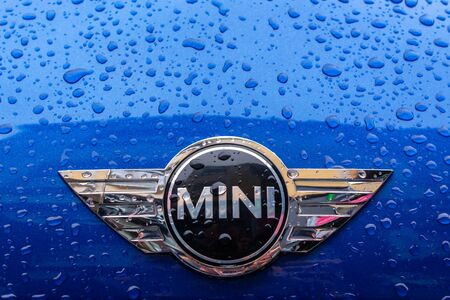 Uzhhorod, ukraine - 14 JUL, 2013: mini cooper logo on the blue metallic hood.  wet vehicle after the rain