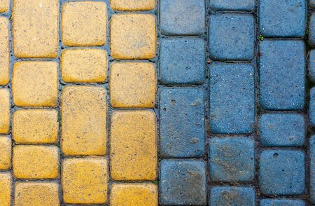 yellow and blue cobbles of pavement texture. stone masonry floor covering. top view of vertical wet grungy background