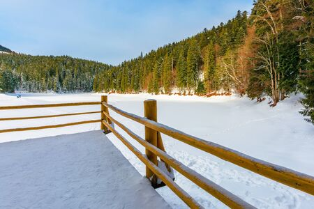 fence on the wooden pier on the lake. wonderful sunny weather in winter. frozen lake synevyr covered with snow. spruce forest on a shore around. beautiful scenery of carpathian mountains Stock Photo - 135534605