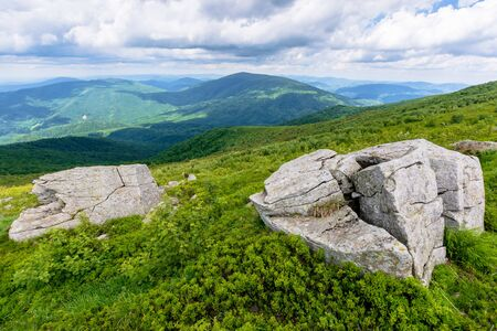 beautiful mountain landscape in summer. rocks on the grassy alpine meadows rolling into distance. clouds on the sky above horizon Stock Photo