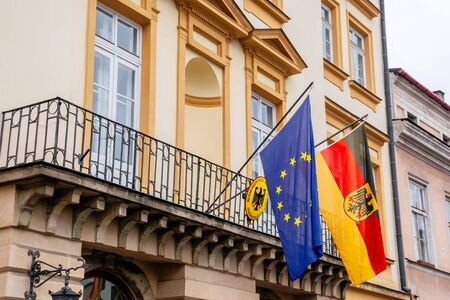 Krakow, poland - APR 30, 2019: German and European Union flags on facade of Consulate General of the Federal Republic of Germany in Krakow located in historic center of an old town