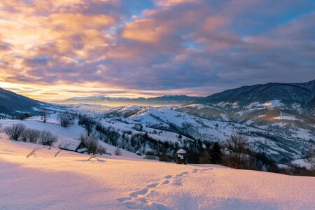 mountainous countryside in winter at sunrise. snow covered hills and fields of carpathian rural area rolling off in to the distant krasna ridge. glowing fog in the valley. colorful clouds on the sky