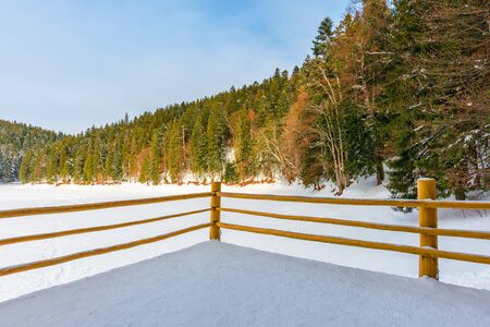 fence on the wooden pier on the lake. wonderful sunny weather in winter. frozen lake synevyr covered with snow. spruce forest on a shore around. beautiful nature of carpathian mountains Stock Photo - 136000272