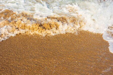 Meereswellen spritzen Schaum am sonnigen Strand. Durcheinander von Salzwasser und Sand im Abendlicht. dynamische Naturtextur Standard-Bild