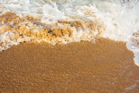 sea waves splash foam on the sunny beach.  mess of salt water and sand in evening light. dynamic nature texture Stock Photo
