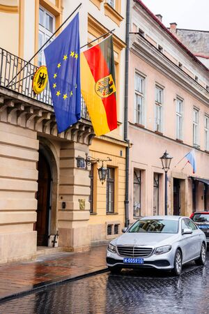 Krakow, poland - APR 30, 2019: German and European Union flags on facade of Consulate General of the Federal Republic of Germany in Krakow located in historic center of an old town. Mercedes car parked on the wet street on an overcast rainy day in springt