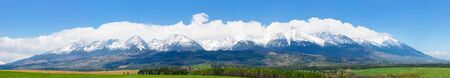 panorama of high tatas mountain ridge in spring. wonderful landscape of slovakia with snow capped peaks. clouds on the blue sky above the massif