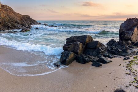 sea beach at sunrise. calm waves wash huge rocks. golden clouds on the sky. stunning marine scenery in morning light. Stock Photo