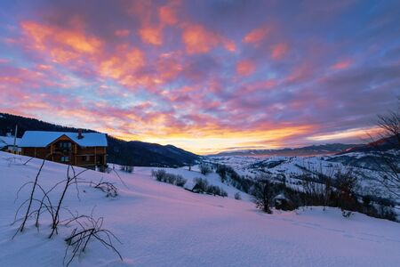 mountainous countryside in winter at dawn. snow covered hills and fields of carpathian rural area rolling off in to the distant krasna ridge. glowing fog in the valley. colorful clouds on the sky Stock Photo - 136867945