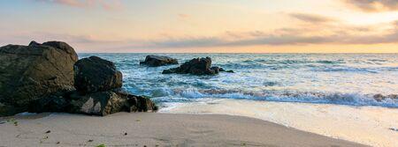 playa del mar al amanecer. olas tranquilas lavan rocas enormes. nubes doradas en el cielo. impresionantes paisajes marinos a la luz de la mañana.