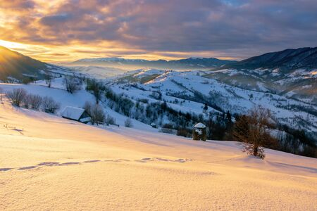 mountainous countryside in winter at sunrise. snow covered hills and fields of carpathian rural area rolling off in to the distant krasna ridge. glowing fog in the valley. colorful clouds on the sky Фото со стока - 137214030