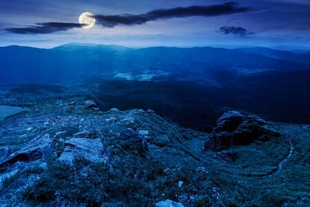 mountain landscape in summer at night. view from the top of carpathian watershed ridge in to the distance in full moon light. boulders on the grassy slopes. weather with clouds on the dark sky Stock Photo