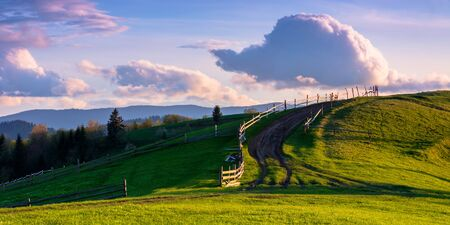 mountainous rural landscape in evening light. wooden fence along the path through rolling hills in fresh green grass. beautiful scenery in springtime. purple clouds on the sky Stock Photo