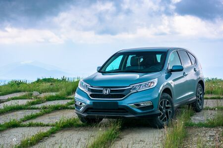mnt. runa, ukraine - JUN 22, 2019: blue suv on a paved meadow. popular AWD vehicle in nature scenery. stormy weather with cloudy sky. take your family anywhere outdoors with honda cr-v concept
