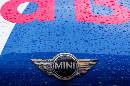 Uzhhorod, ukraine - 14 JUL, 2013: Red Bull mini cooper publicity car logo. fancy car tuning used for promotion. wet advertisement vehicle after the rain