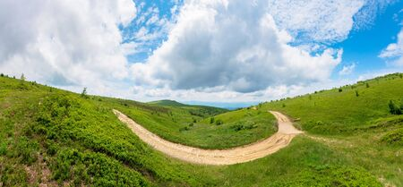 mountain dirt road scenery. path through the grassy meadows on rolling hills. ridge in the distance. green carpathian landscape. cloudy summer weather. dramatic sky