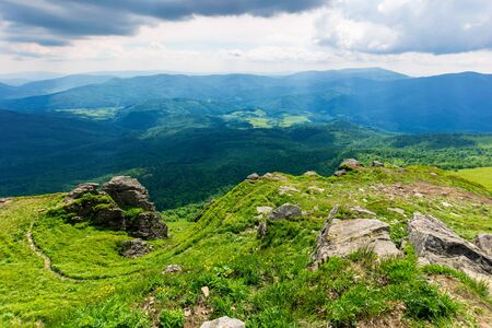 mountain landscape in summer. view from the top of carpathian watershed ridge in to the distance. boulders on the green grassy slopes. sunny weather with clouds on the blue sky Stock Photo