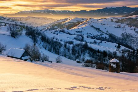 mountainous countryside in winter at sunrise. snow covered hills and fields of carpathian rural area rolling off in to the distant krasna ridge. glowing fog in the valley. colorful clouds on the sky Stock Photo - 138192053