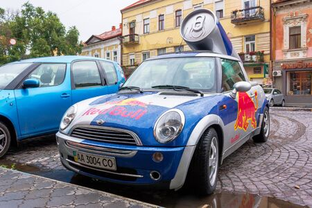 Uzhhorod, ukraine - 14 JUL, 2013: Red Bull mini cooper publicity car with a can of energy drink behind. fancy car tuning used for promotion. wet advertisement vehicle after the rain
