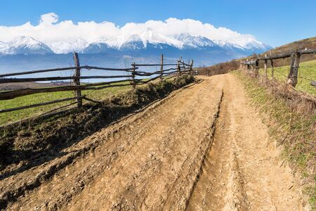 rural landscape in spring. composite landscape of mountain ridge in the distance with snow capped tops and fields with fence along the country dirt road. warm sunny weather Stock Photo