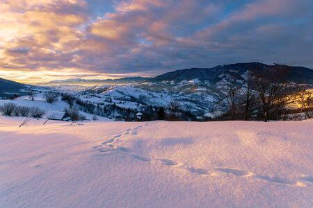 mountainous countryside in winter at sunrise. snow covered hills and fields of carpathian rural area rolling off in to the distant krasna ridge. glowing fog in the valley. colorful clouds on the sky Stock Photo - 138192120