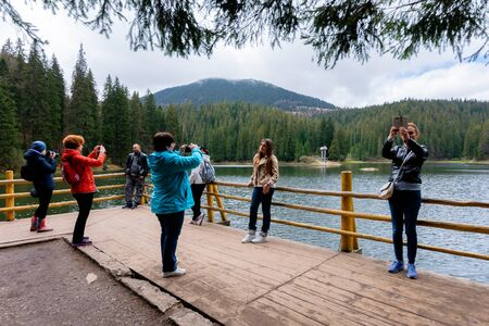 synevir national park, ukraine - MAY 09, 2017: people enjoying the beauty of Carpathian landscape. natural mountain lake attracts thousands of tourist to observe, relax and take selfies for memories Stock Photo - 141652049