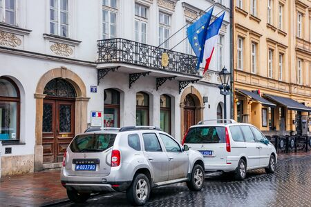 Krakow, poland - APR 30, 2019: France and European Union flags on facade of Consulate General of the Republic of France in Krakow located in historic center of an old town. Renault and Citroen cars parked on the wet street on an overcast rainy day in spri Editorial