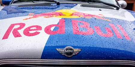 Uzhhorod, ukraine - 14 JUL, 2013: Red Bull mini cooper publicity car detail. fancy car tuning used for promotion. wet advertisement vehicle after the rain Editorial