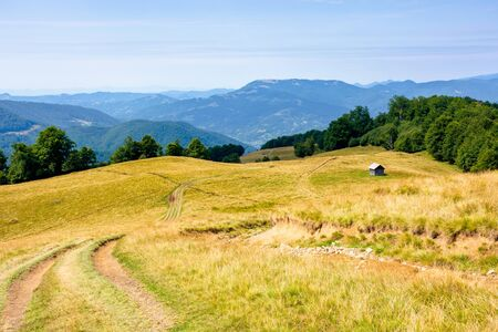 mountainous countryside in summertime. country road down the hill through the grassy meadow. woodshed on the path. sunny weather with cloudless sky. explore back country concept Stock Photo - 138617858