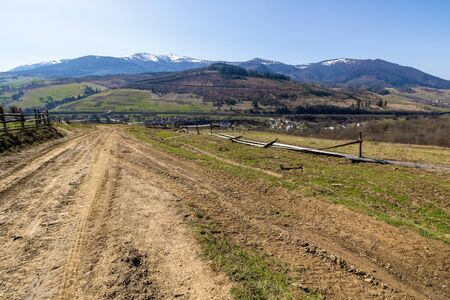 rural landscape in spring.  mountain ridge in the distance with snow capped tops and fields with fence along the country dirt road. warm sunny weather