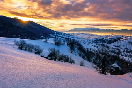 mountainous countryside in winter at sunrise. snow covered hills and fields of carpathian rural area rolling off in to the distant krasna ridge. glowing fog in the valley. colorful clouds on the sky Stock Photo - 138937760
