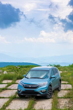 mnt. runa, ukraine - JUN 22, 2019: blue suv on a paved meadow. popular AWD vehicle in nature scenery. stormy weather with cloudy sky. take your family anywhere outdoors with honda cr-v concept Stock Photo - 141904808